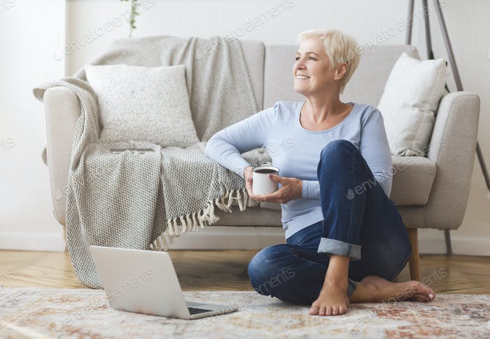 Elderly business lady enjoying cup of coffee at home