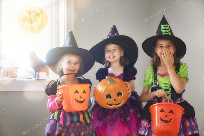 Laughing children in witches costumes.
