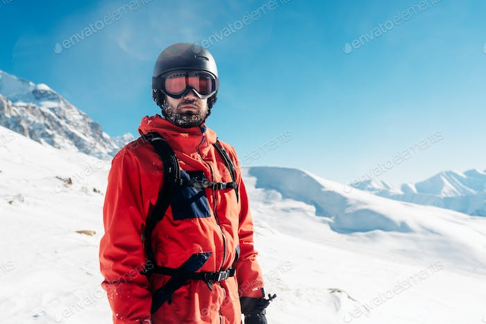 serious snowboarder is standing in the red suit