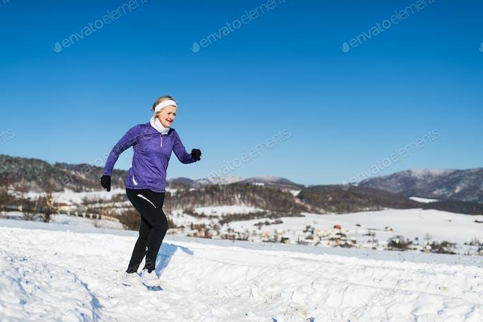 Senior woman jogging in winter nature. Copy space.