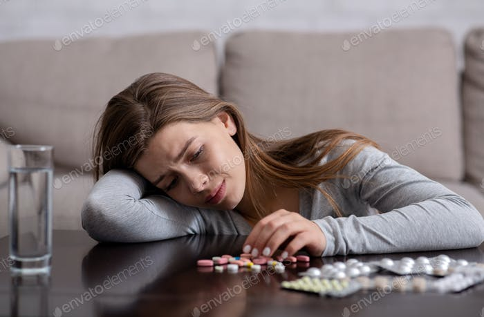 Depressed millennial woman committing suicide by overdosing on sleeping pills, indoors
