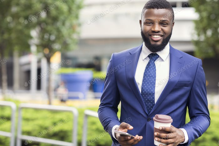 Cheerful african employee having coffee break and using smartphone outdoors