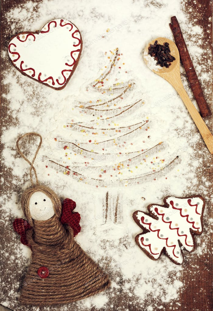 Gingerbread cookies, spices and flour over wooden background