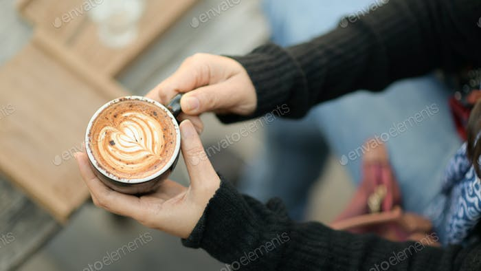 Coffee latte heart texture in hand of tourists.
