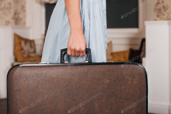 Female hand holding suitcase.