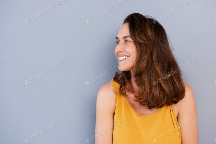 Close up beautiful older woman smiling against gray wall