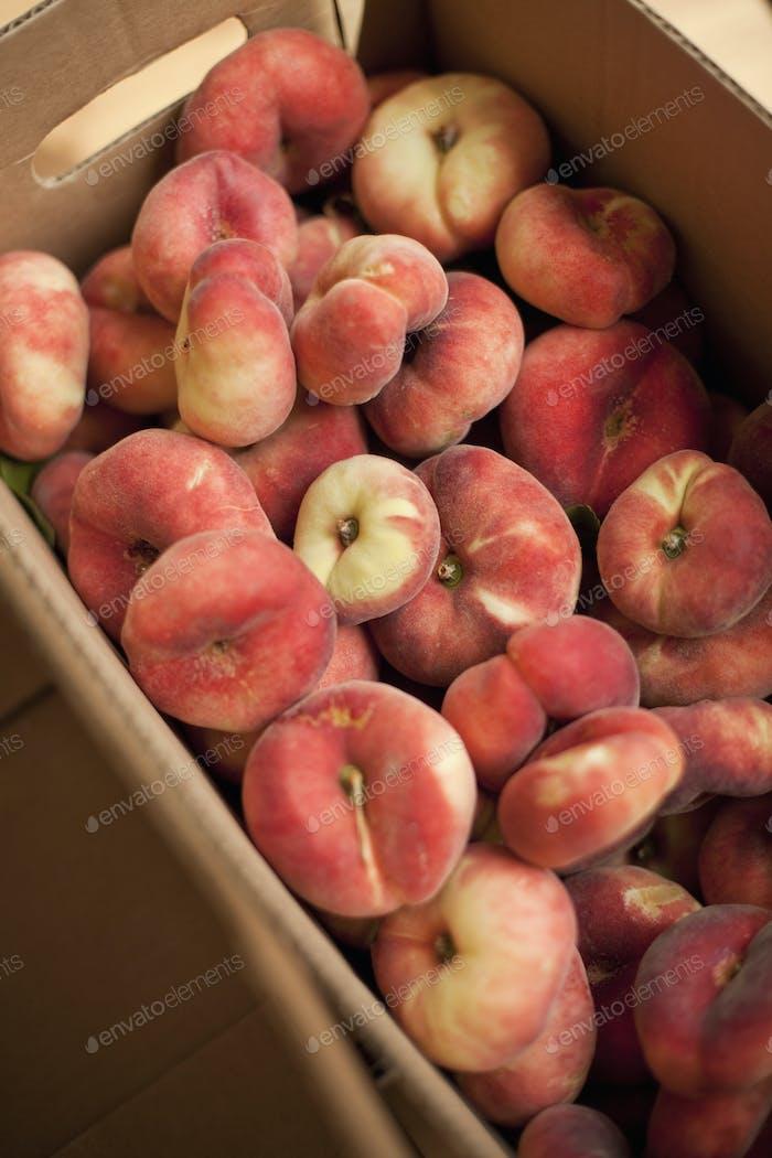 Fresh fruit on an organic farmstand. Doughnut peaches in a box.