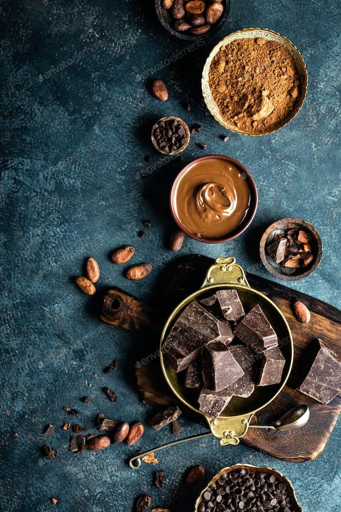 Dunkle Schokoladenstücke zerkleinert und Kakaobohnen. Schokoladenhintergrund