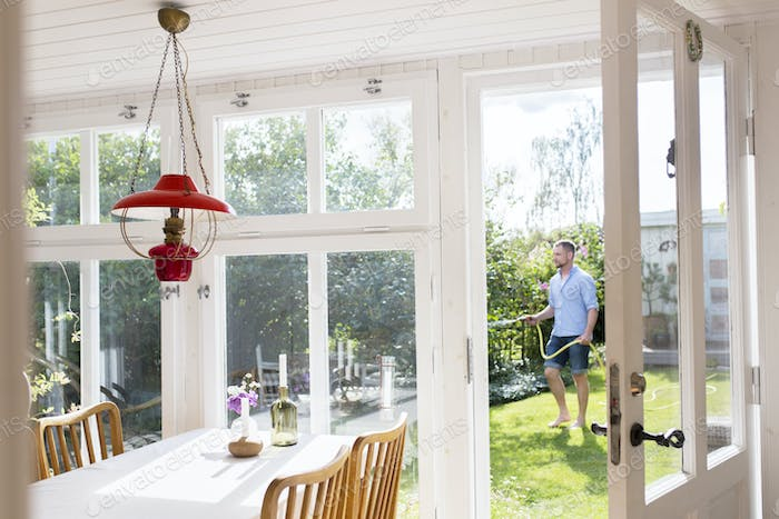 Man watering plants with garden hose, view from house interior
