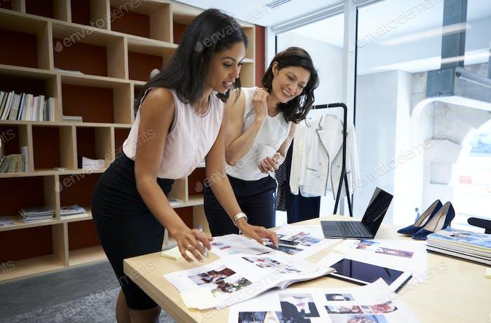 Zwei weibliche Kreative diskutieren Zeitschriftenlayout in einem Büro