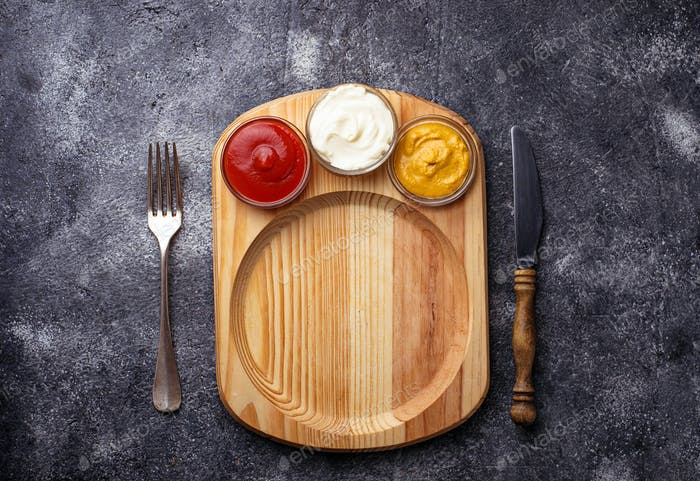 Food background with mustard, ketchup, mayonnaise, fork and knife.
