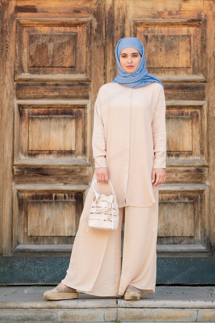 Pretty young muslim woman on background of wooden door
