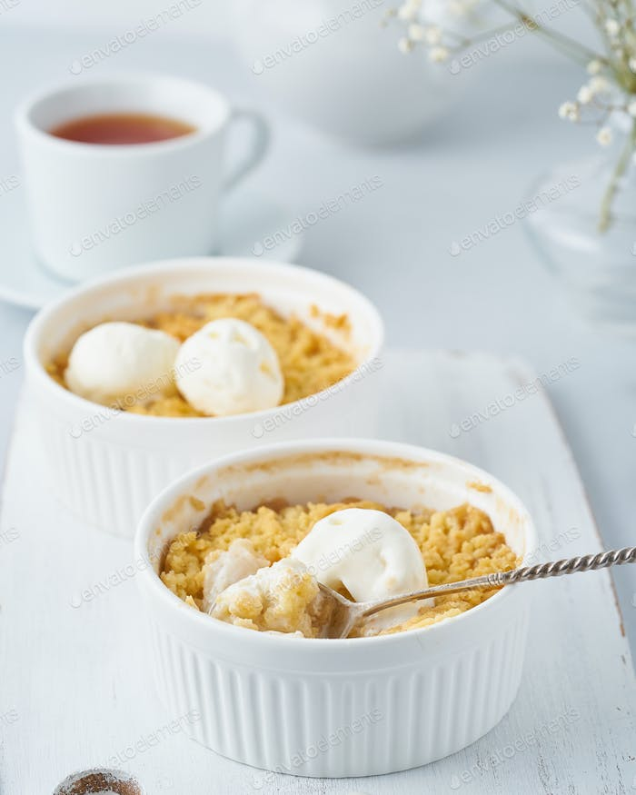 Apple crumble with ice cream, spoon with streusel. Side view, vertical. Morning breakfast