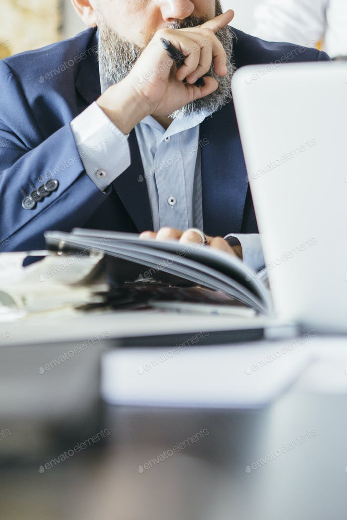 unrecognizable man with pen and magazine