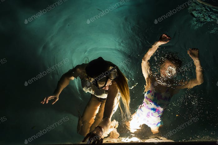 Two children swimming in pool at night
