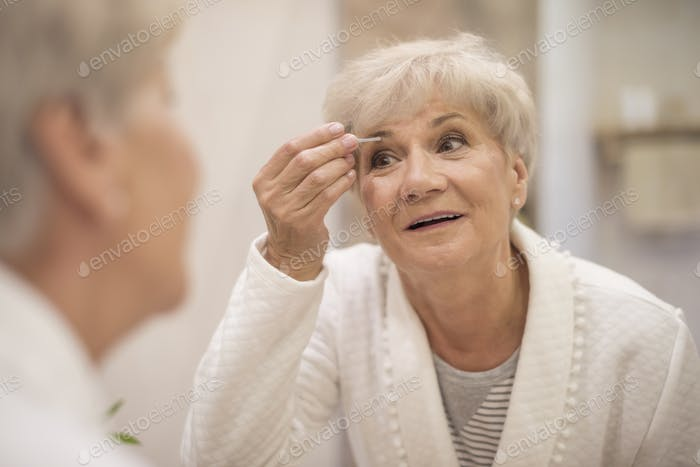 Well-groomed woman in front of the mirror