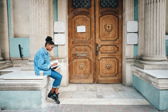 African American student girl in denim jacket with book thoughtfully studying near old door