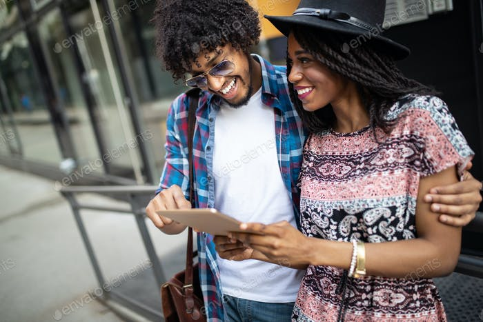 Attractive young african students are using a digital tablet and smiling while standing outside