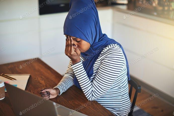 Junge arabische Unternehmerin sitzt zu Hause und sieht gestresst aus