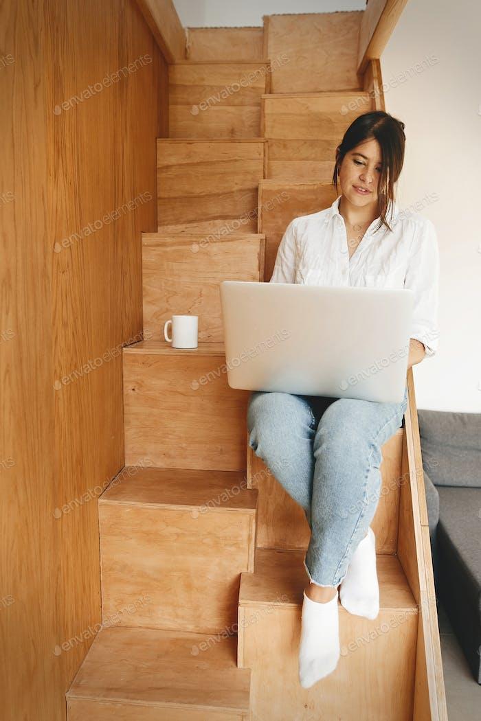 Junge Geschäftsfrau arbeitet online von zu Hause aus und lächelnd
