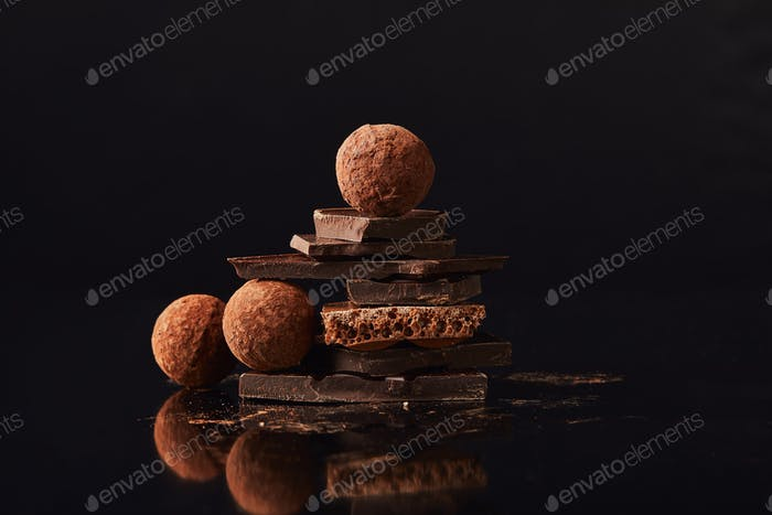close up view of arrangement of truffles and chocolate bars on black