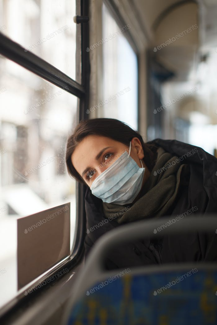 caucasian female with medical mask in urban transport