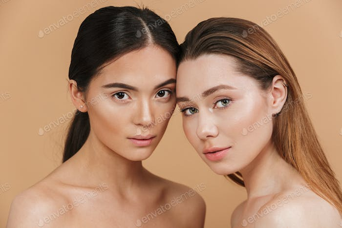 Beauty portrait closeup of two different nation women, asian and