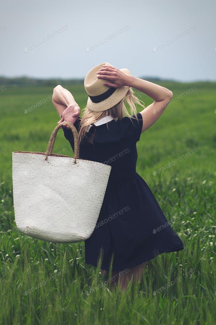 Frau mit schwarzem Kleid in einem Feld von grünem Weizen