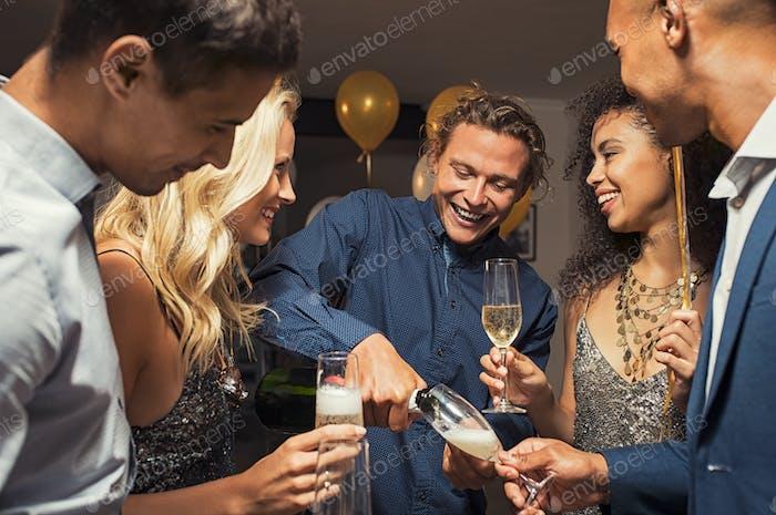 Mann gießt Champagner in Flöten