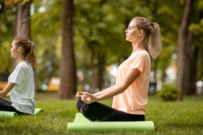 Young slender girl sits in the lotus position with closing eyes doing exercises with other girls on