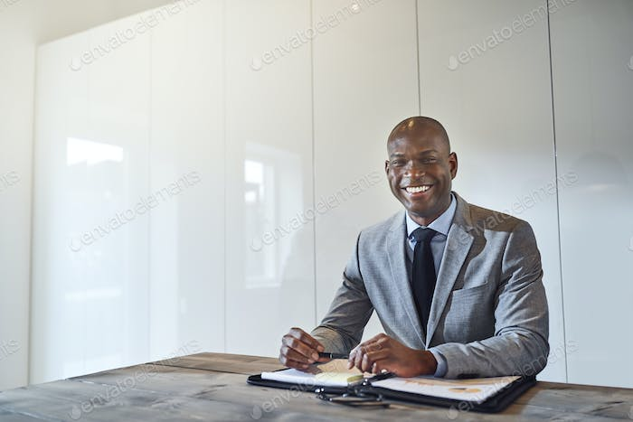 Smiling African American businessman sitting with paperwork in a boardroom
