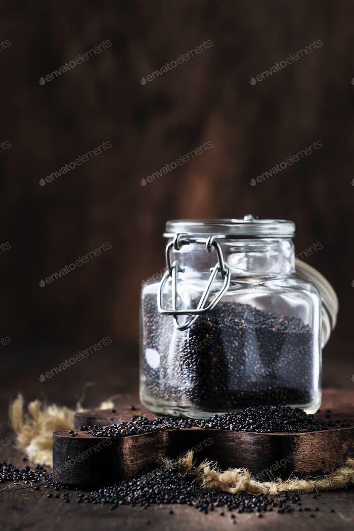 Black raw quinoa seeds in glass jar