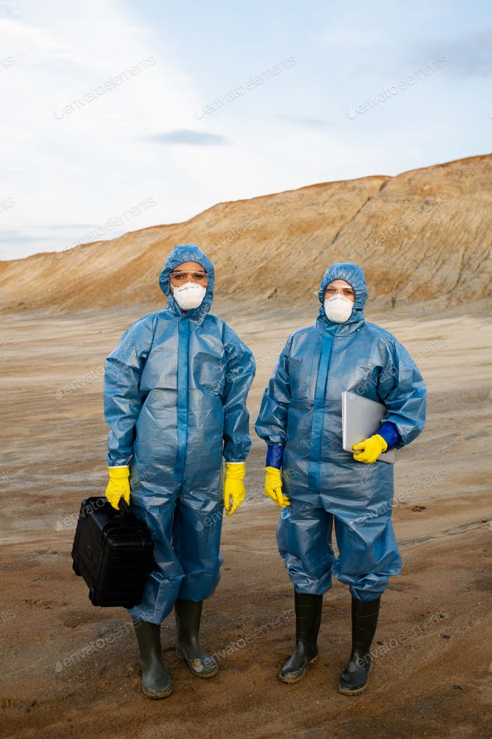 Two young female researchers in protective workwear standing on polluted soil