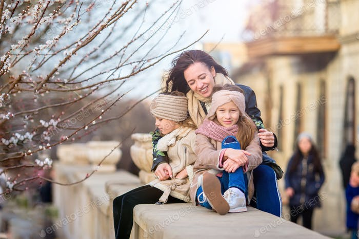 Mother and little daughters outdoor in city