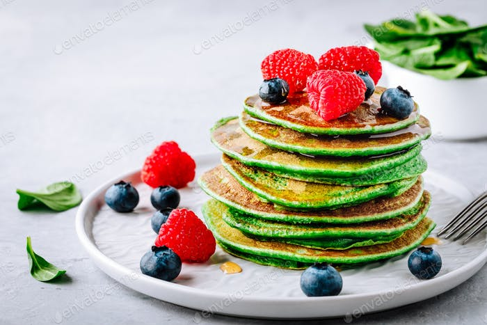 Healthy green spinach pancakes with raspberries, blueberries and honey