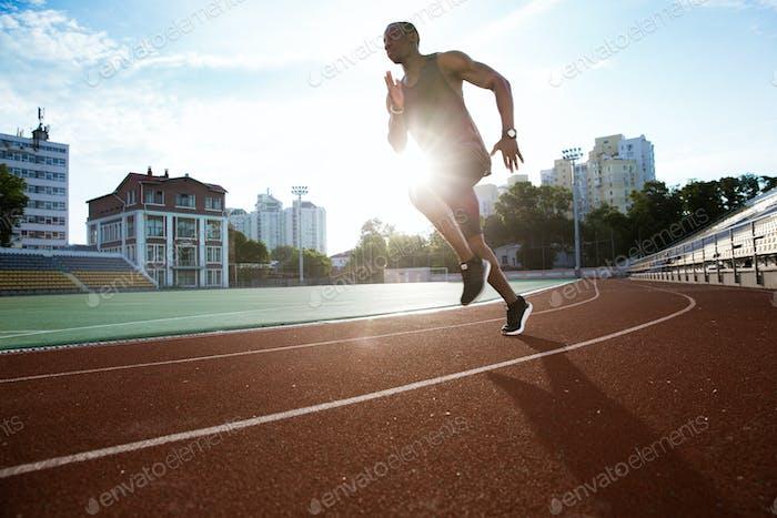 Male runner practicing his sprint in athletics stadium racetrack