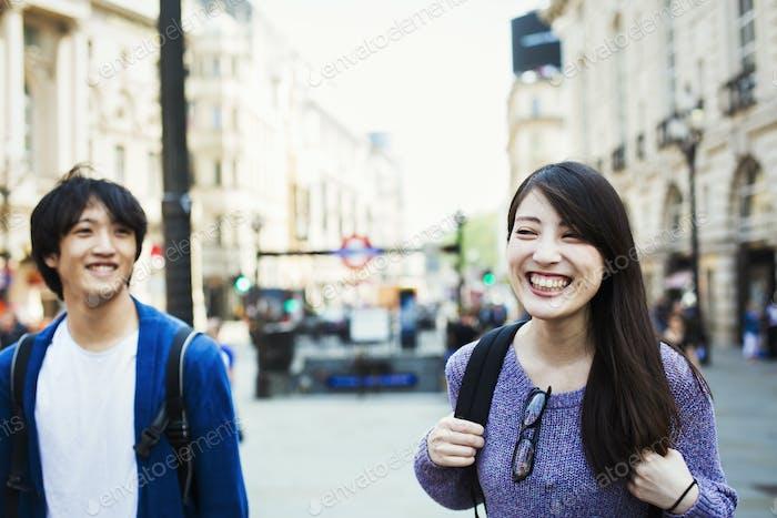 Молодой японский мужчина и женщина наслаждаются днем в Лондоне, гуляя возле Пикадилли цирка.