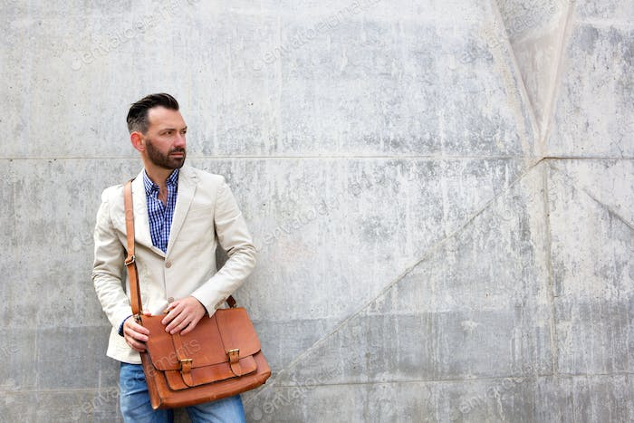 Stylish mature man standing against wall
