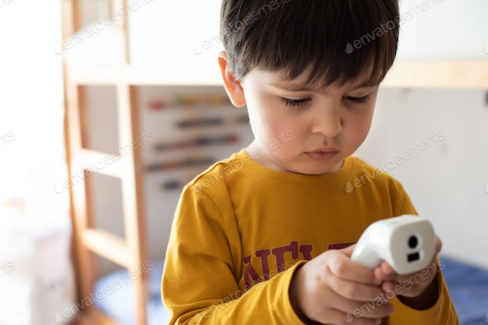 Little boy using a digital thermometer