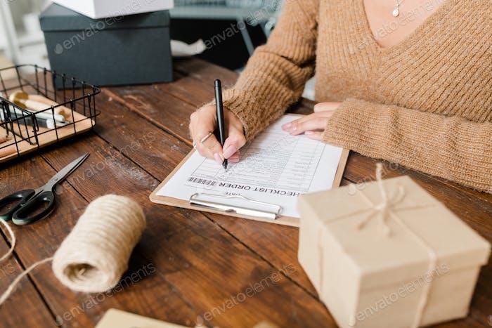 Female customer in pullover putting ticks opposite ordered goods in checklist