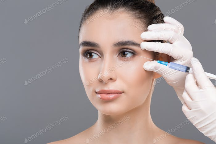 Portrait of attractive young woman making cosmetic injections