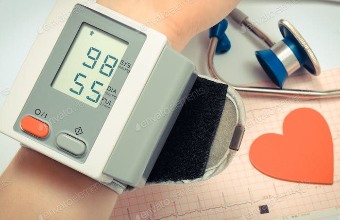 Measuring blood pressure and medical stethoscope with heart shape on electrocardiogram graph
