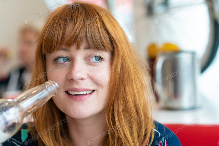 Portrait of ginger girl with blue eyes holding a beer on a floral dress in a diner