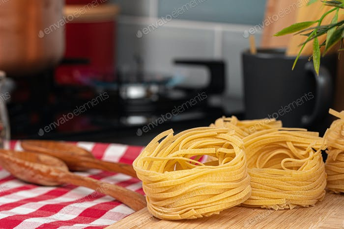 Dry spaghetti on a kitchen counter with cooking utensils
