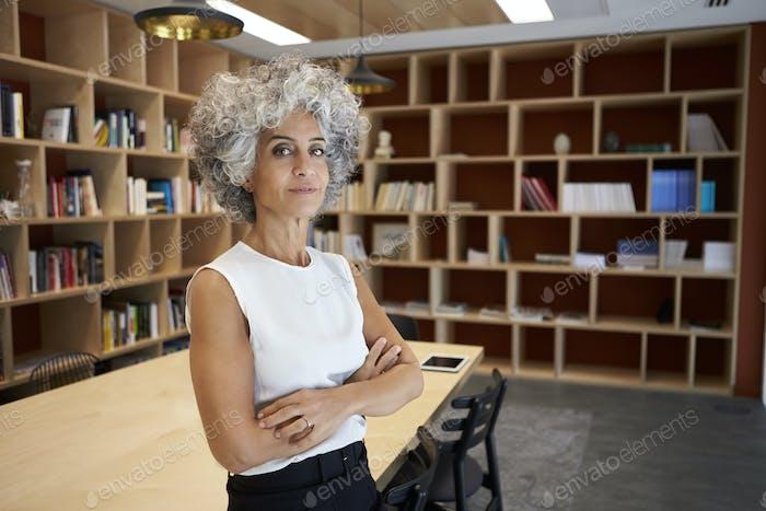 Senior Geschäftsfrau stehend im Sitzungssaal auf der Suche nach Kamera