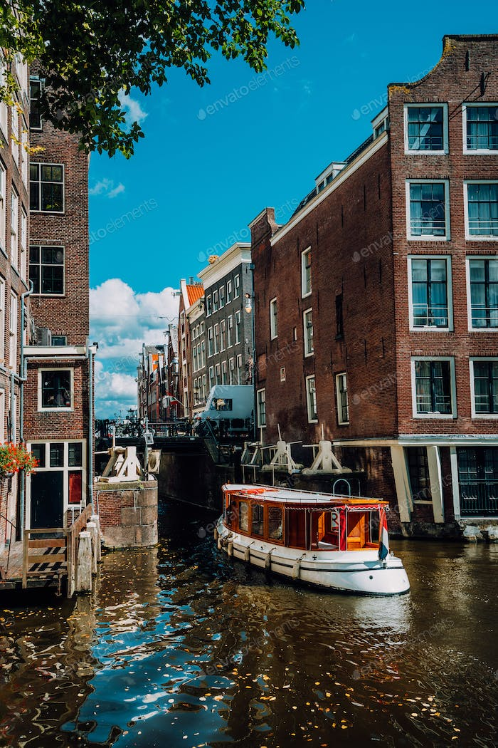 Small Tourist boat floating picturesque dutch channel passing traditional brick houses. Colorful