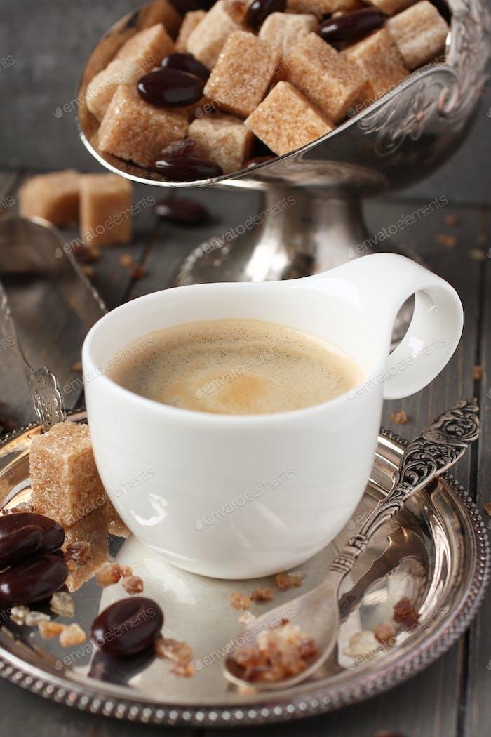 Tasse Espresso, Zuckerwürfel und Schokoladenbonbons auf rustikalem Holzhintergrund