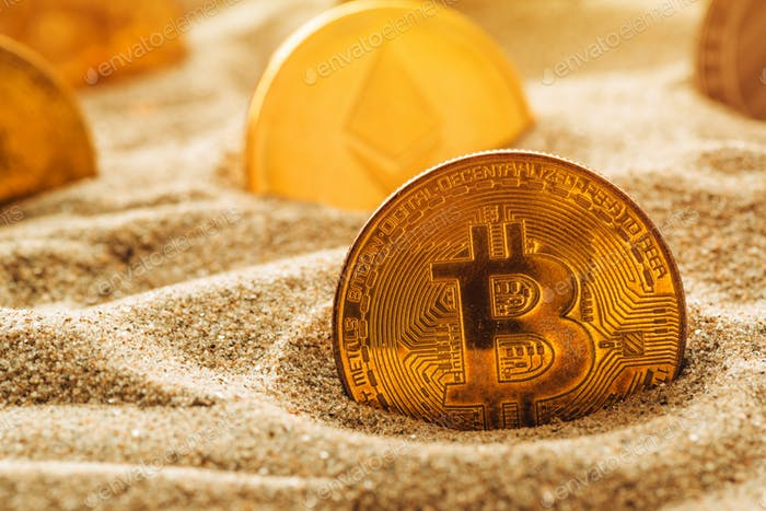 Golden bitcoin in sand