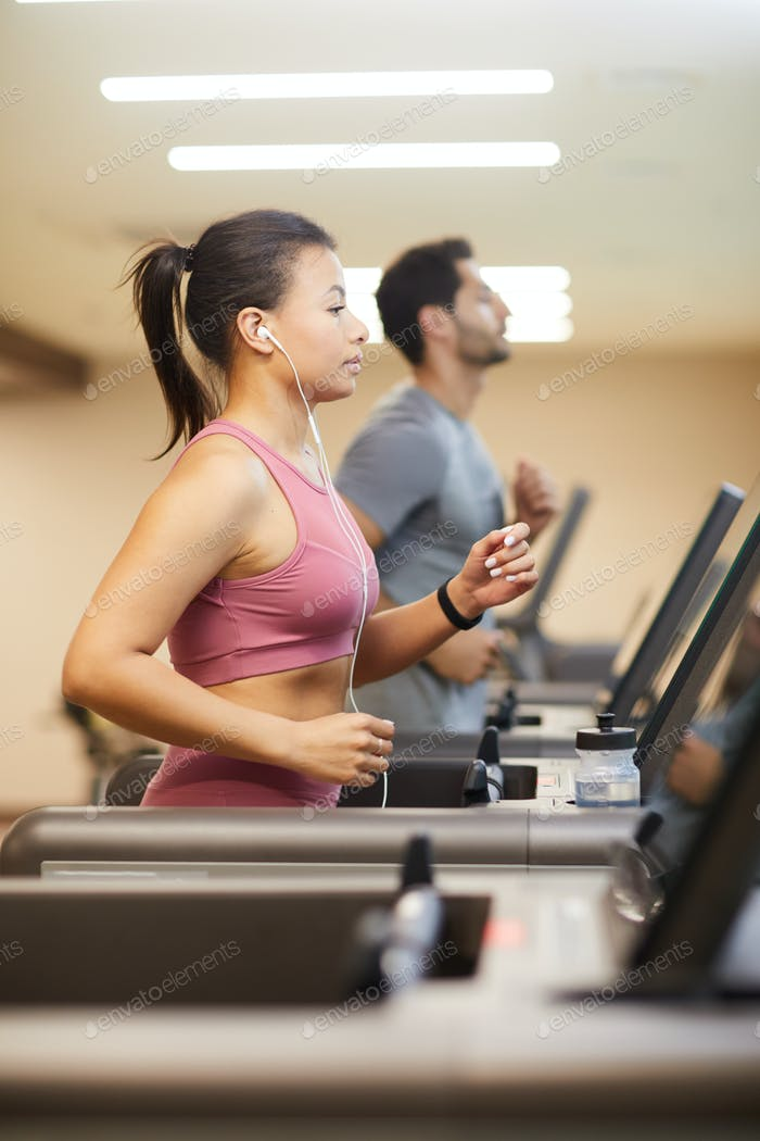 Two People Running on Treadmills in Gym