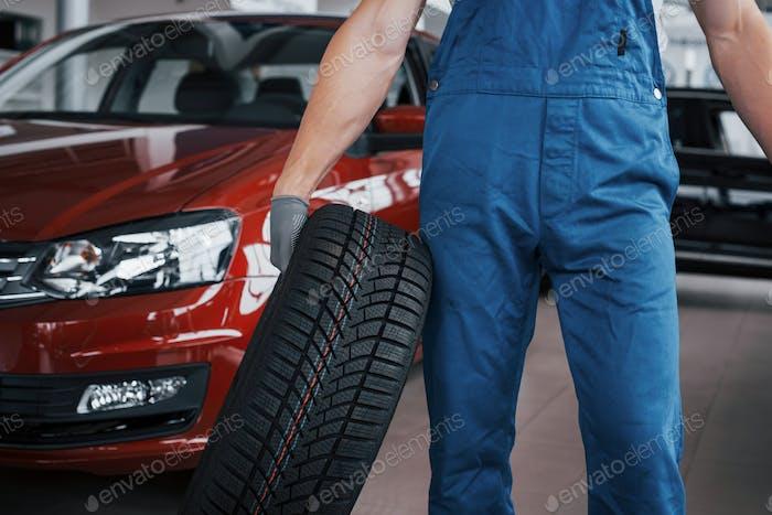 Mechaniker hält einen Reifenreifen in der Reparaturwerkstatt. Ersatz von Winter- und Sommerreifen